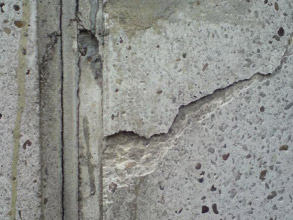 Spalled concrete on chimney stack due to moisture ingress
